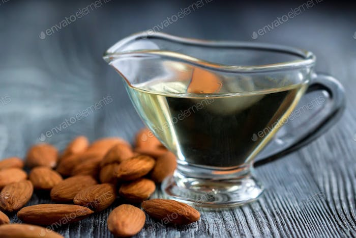 Sweet almond oil in glass jar and kernels