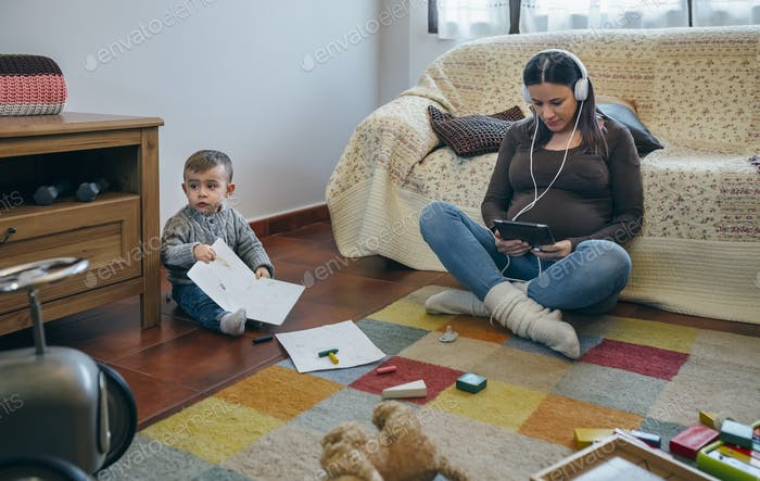 Pregnant using the tablet while her son is playing