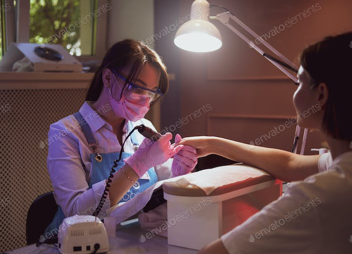 Young manicurist is working at her workplace with customer.