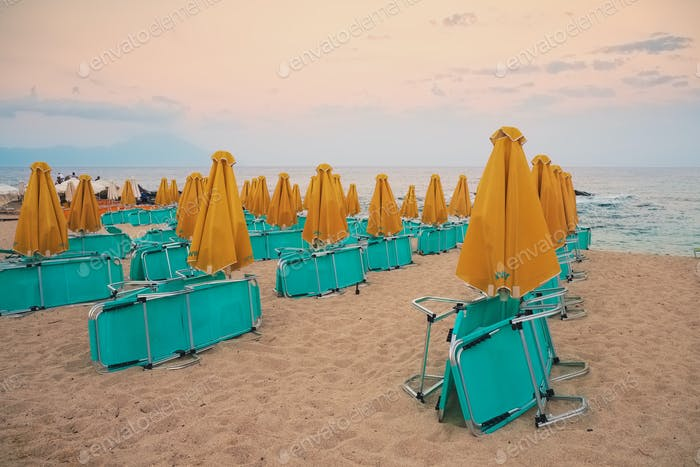 Collapsed deck chairs and umbrellas on the beach