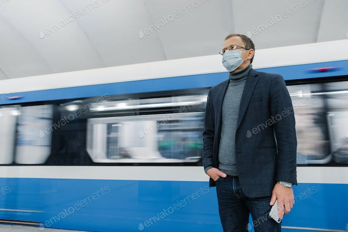Businessman wears surgical sterile mask, poses against underground train