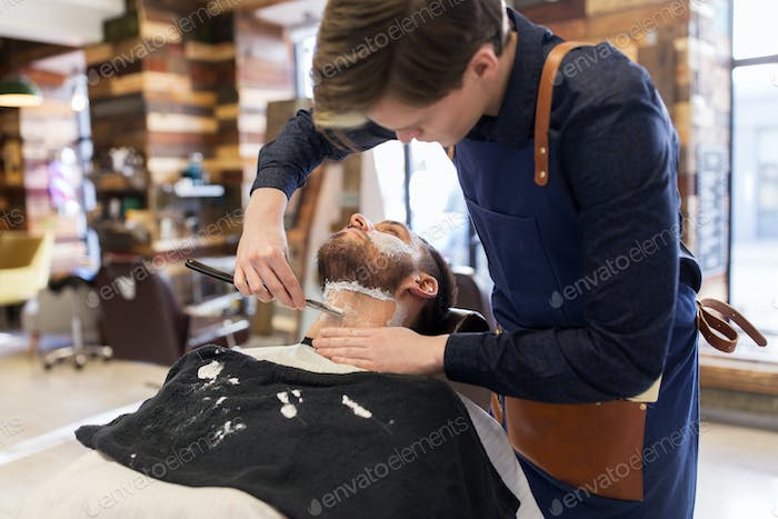 barber with straight razor shaving clients beard