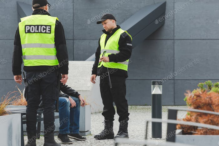 Two police officers talking to man on the street