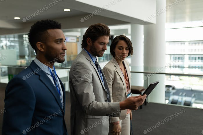 Businessman standing and looking at digital tablet in lobby at office