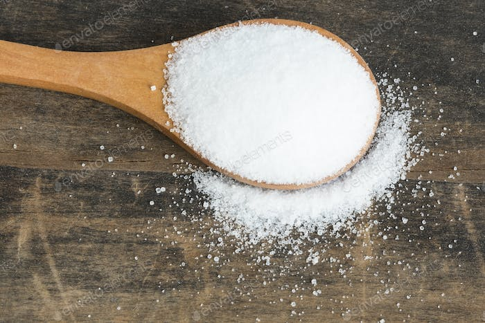 Salt in a Wooden Spoon on a Rustic Background