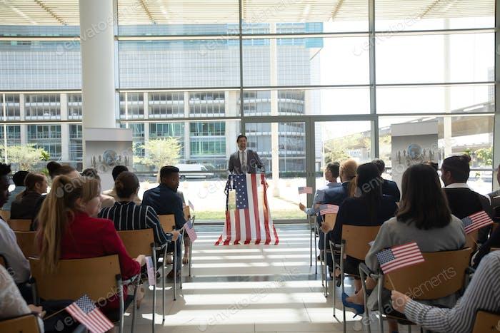 Geschäftsmann spricht auf Business-Seminar im Bürogebäude mit amerikanischen Flaggen