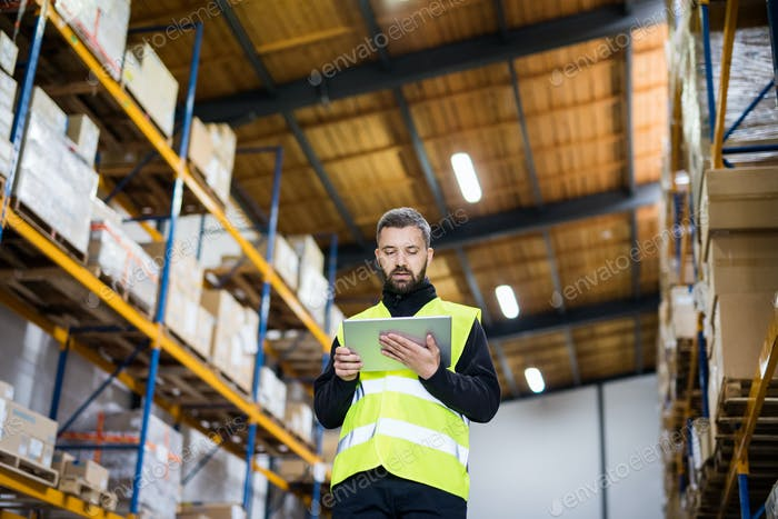 Male warehouse worker with tablet.