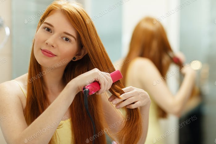 Beautiful Woman Ironing Healthy Red Hair With Iron Straightener