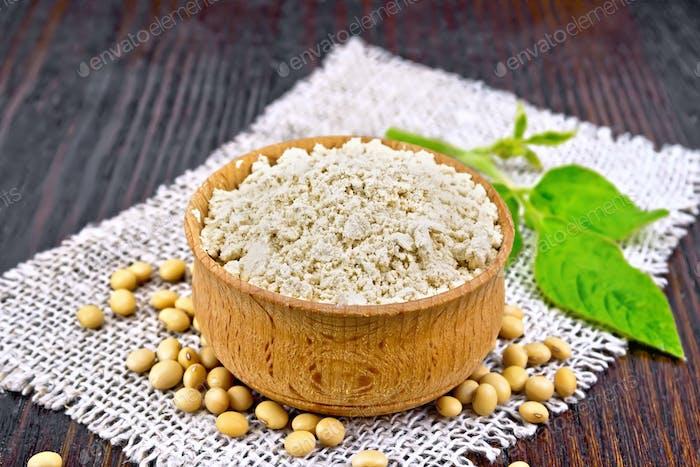 Flour soy in bowl with leaf on dark board