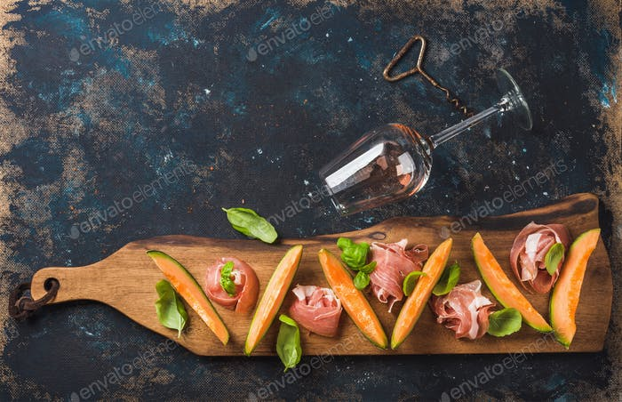 Prosciutto, cantaloupe melon and wine glass over dark plywood background