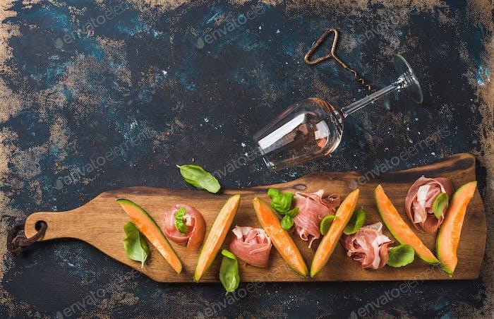 Prosciutto, Melone Melone und Weinglas auf dunklem Sperrholz Hintergrund
