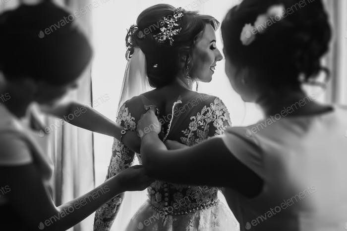 Bridesmaids helping stylish happy bride fit in dress