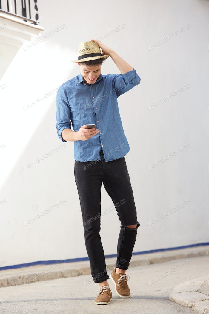 Cheerful guy walking and reading text message on cell phone