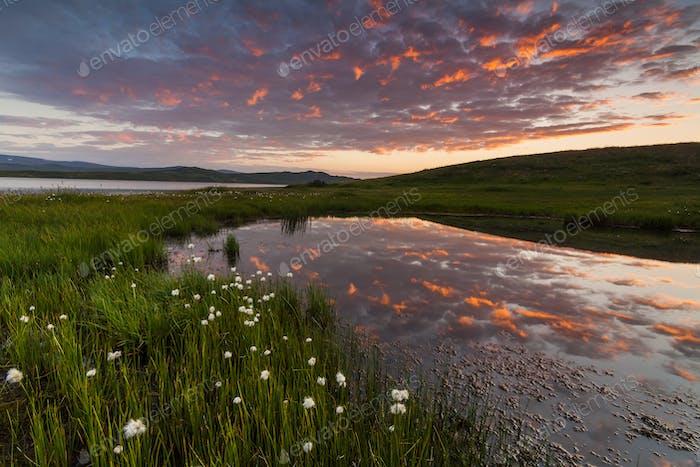 Malerischer Sonnenuntergang über den Bergen und dem See