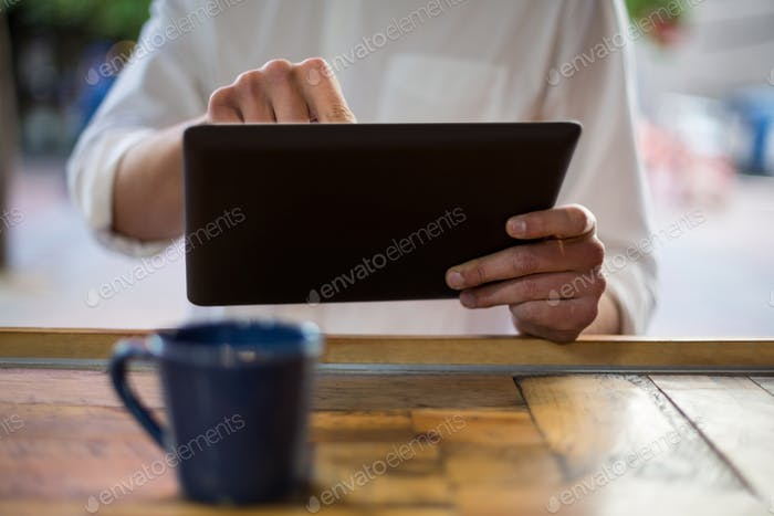 Mid-section of man using digital tablet at counter