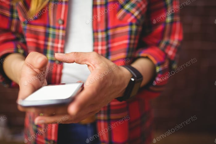 Hipster using her smartphone on red brick background