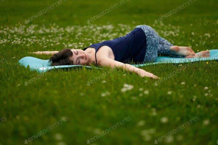 Beautiful caucaisan young woman working out outdoors on blue mat. Jathara Parivartanasana top view