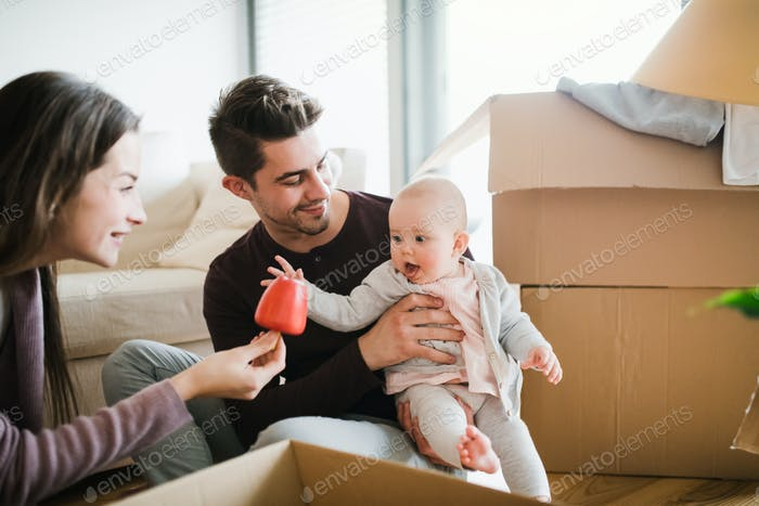 Young couple with a baby and cardboard boxes moving in a new home.