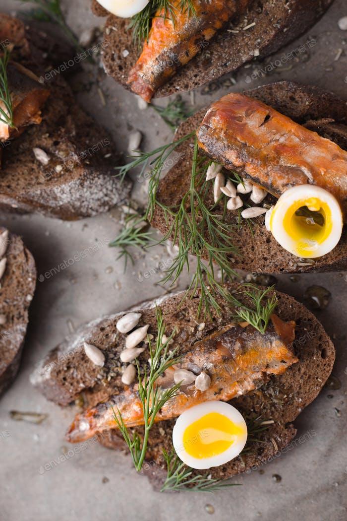 Sardines, quail egg on rye bread diagonal