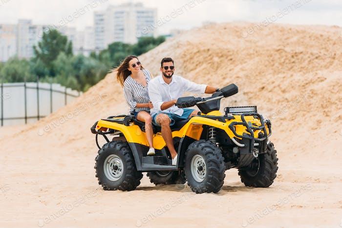 glückliches aktives junges Paar fährt Geländefahrzeug in der Wüste