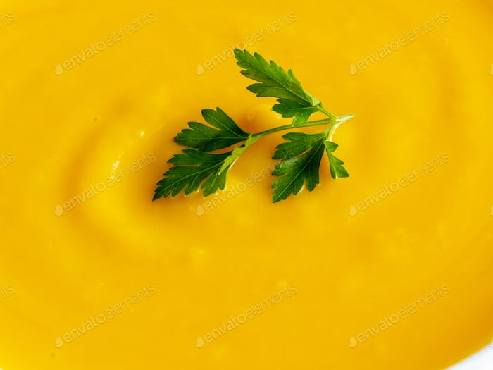 bright orange pumpkin soup with greens, macro
