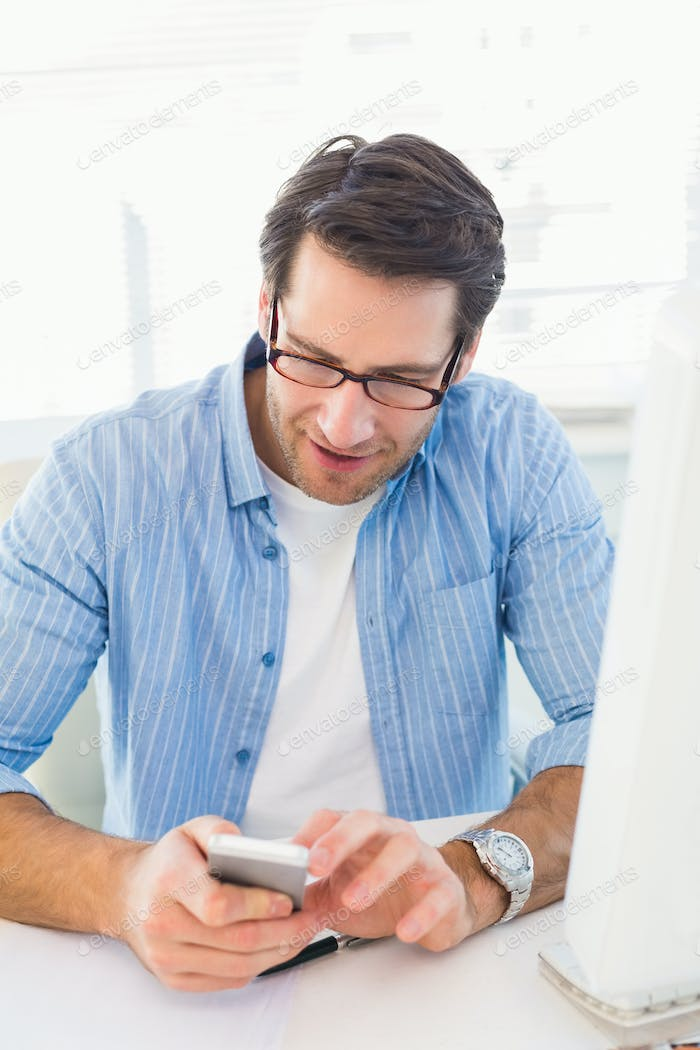 Male photo editor typing text message in office