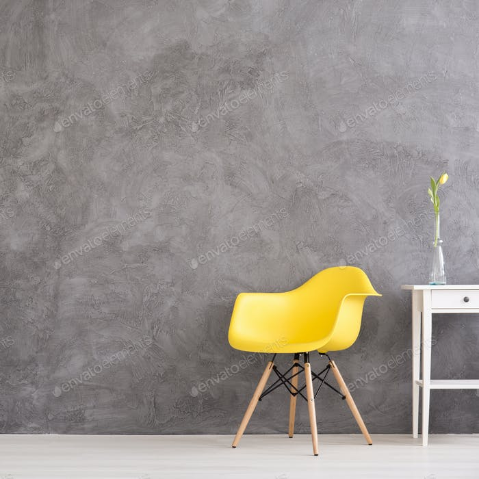Yellow chair in grey wall interior
