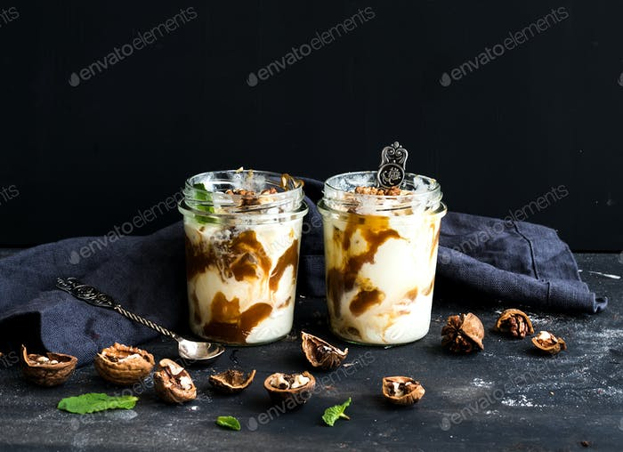 Walnut and salted caramel ice-cream in glass jars with fresh mint over dark grunge backdrop