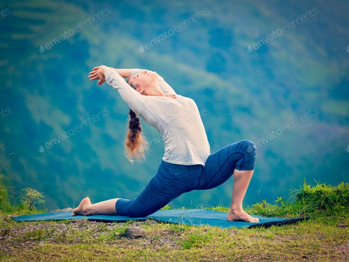 Sporty fit woman practices yoga asana Anjaneyasana in mountains