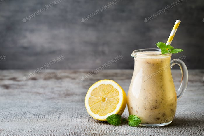 Banana and lemon smoothie, on the grey  background.