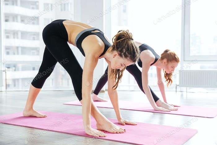 Two women doing exercises in yoga center
