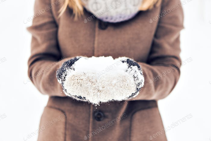 Close-up of winter woman with snow