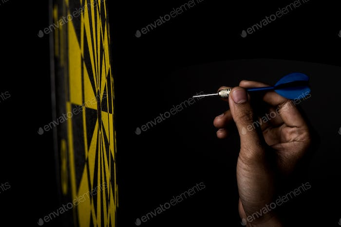 dartboard with arrow on black background, success concept