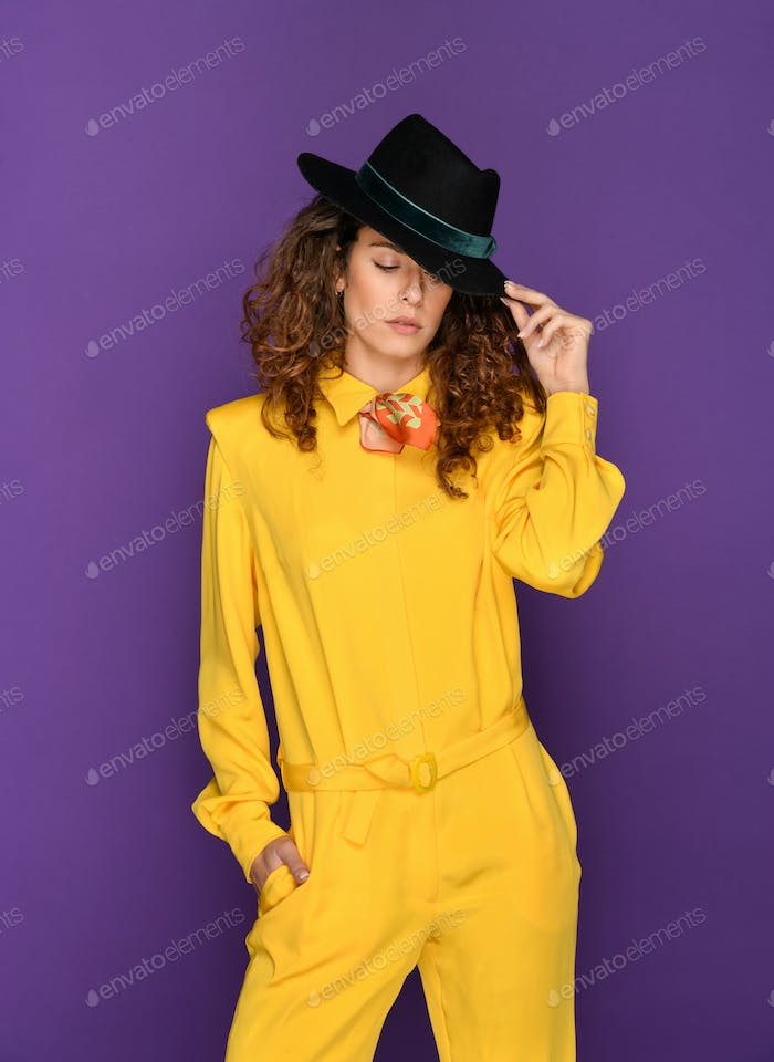 Fashionable woman in yellow 80s suit and hat