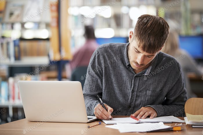 Mature Male Student Working On Laptop In College Library