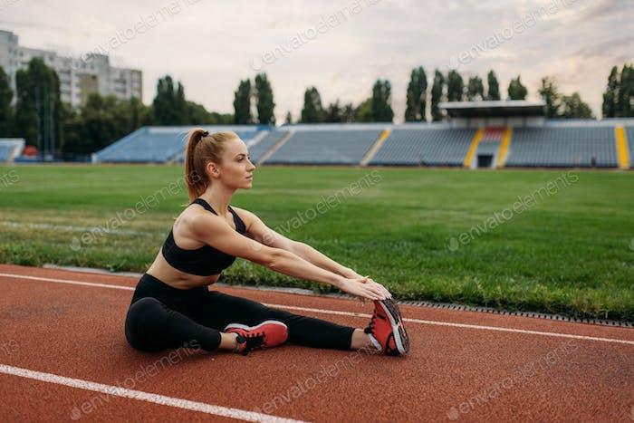 Female runner in sportswear, training on stadium
