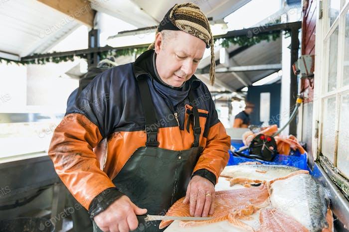 Mature fisherman filleting salmon in fishing industry