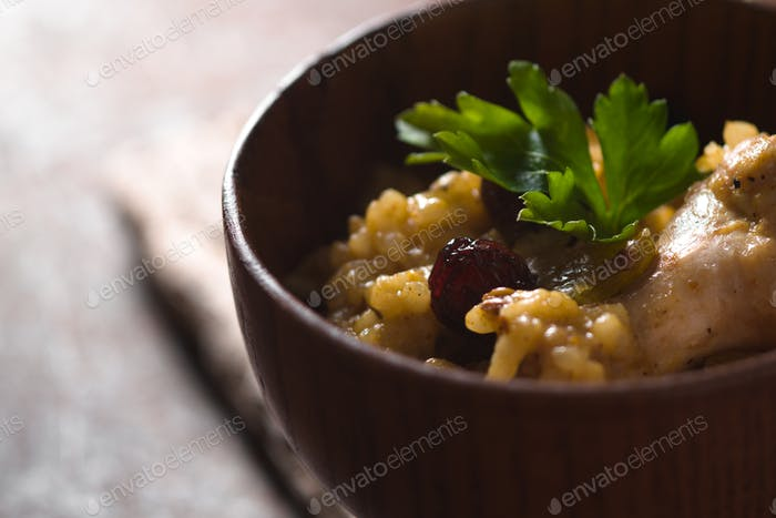 Pilaf with rice, chicken and raisins in a wooden bowl closeup