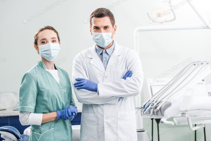 dentists in masks standing with crossed arms in dental clinic