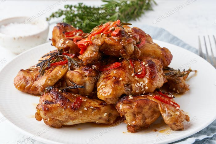 Barbecue chicken wings. Oven baked chiken on plate. Hot korean food. Side view, close up