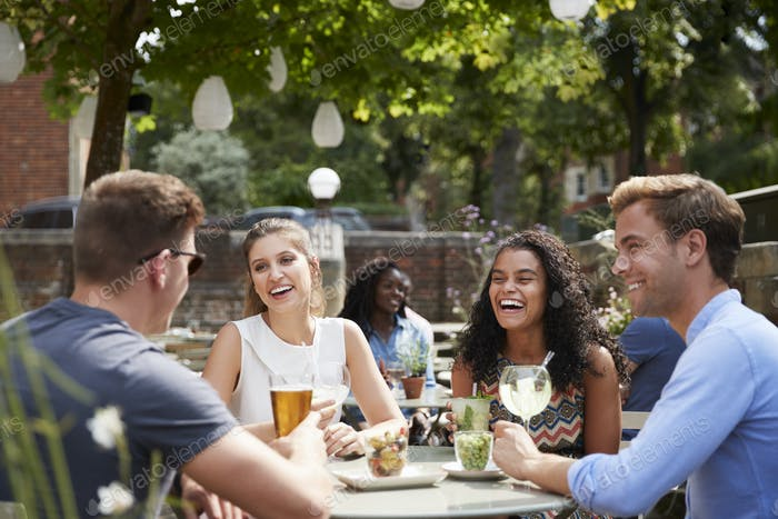 Freunde sitzen am Tisch in Pub Garten genießen Getränke zusammen