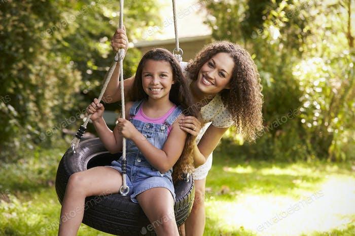 Mutter schieben Tochter auf Reifen Schaukel in Garten