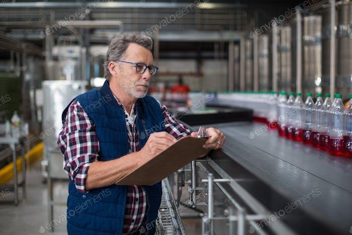 Männliche Fabrikarbeiter Aufrechterhaltung Rekord auf Zwischenablage in der Fabrik