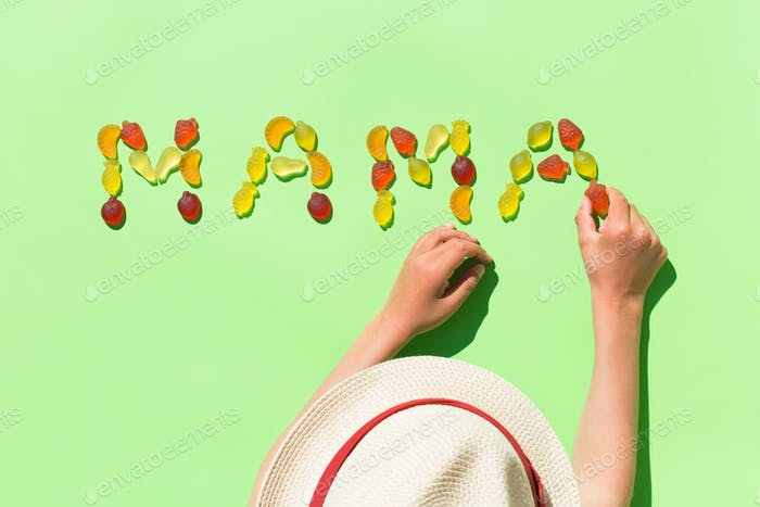 Childs hands making word mama with jelly candies