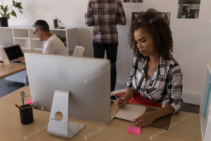 Front view of young mixed-race female executive writing in diary at desk in modern office