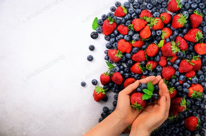 Hands holding fresh berries. Healthy clean eating, dieting, vegetarian food, detox concept. Close up