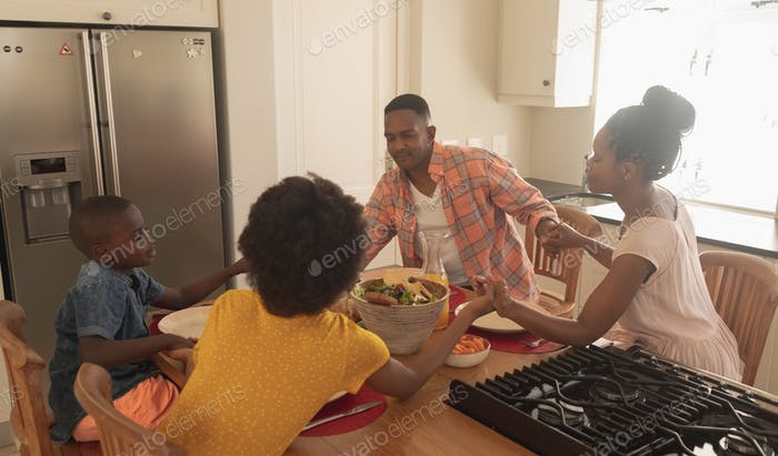 Happy family holding hands and praying together at dining table in a comfortable home