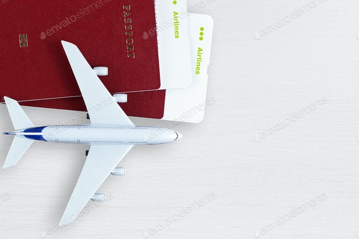 Boarding passes, passports and toy plane on table