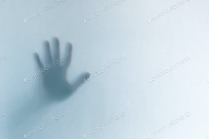Defocused scary ghost hands behind a white glass background