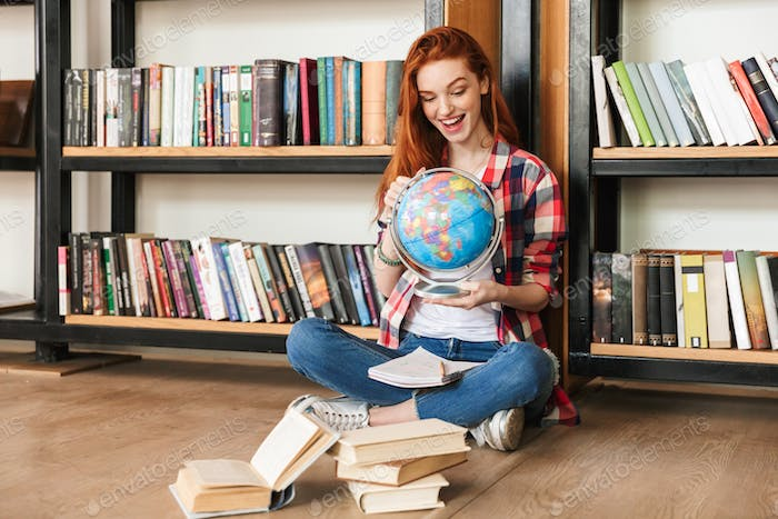 Excited teenage girl holding globe